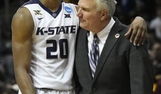 Kansas State forward Xavier Sneed (20) embraces Kansas State head coach Bruce Weber after a regional final NCAA college basketball tournament game against Loyola-Chicago, Saturday, March 24, 2018, in Atlanta. Loyola-Chicago won 78-62. (AP Photo/John Amis)