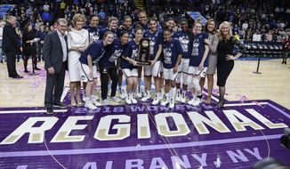 Connecticut head coach Geno Auriemma, left, poses for photographs with with his team following a women's NCAA college basketball tournament regional final game against South Carolina at the a women's NCAA college basketball tournament Monday, March 26, 2018, in Albany, N.Y. Connecticut won 94-65. (AP Photo/Frank Franklin II)