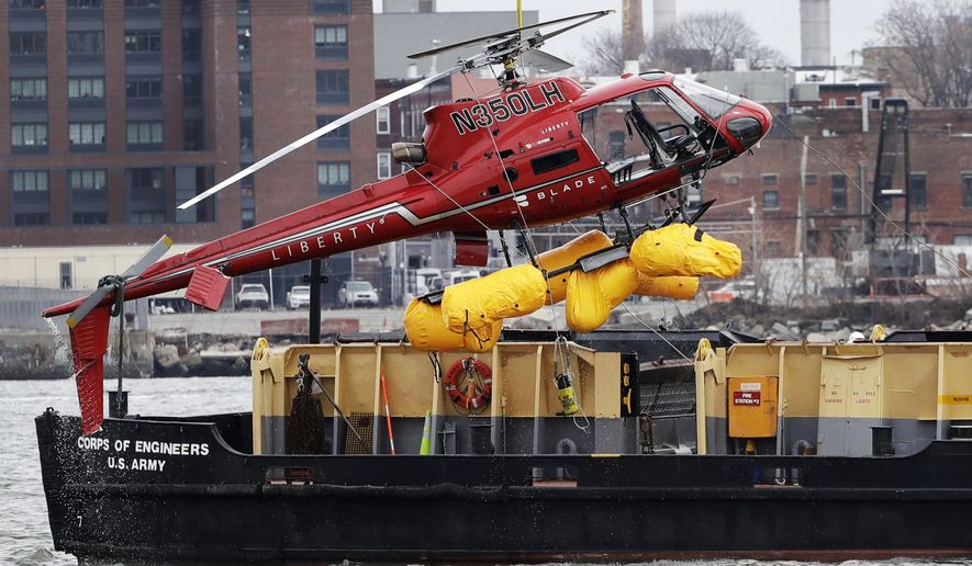 FILE - In this March 12, 2018 file photo, a helicopter, which crashed the previous day, is hoisted by crane from the East River onto a barge, in New York. The pilot of the helicopter that crashed into New York City's East River told federal investigators that he believed the aircraft's fuel was cut off when a passenger's restraint tether tangled with an emergency fuel cutoff shift. The pilot told the National Transportation Safety Board that he went to flip off the switch because the craft was going down, but discovered that it was already off and that part of the harness was underneath it.  (AP Photo/Mark Lennihan, File)