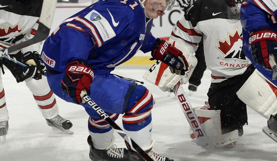 FILE - In this Dec. 29, 2017, file photo, United States forward Casey Mittelstadt (11) chases a loose puck during the overtime period of a preliminary round game against Canada at the IIHF World Junior Championship in Orchard Park, N.Y.  The Buffalo Sabres have reached an agreement with their top prospect, center Casey Mittelstadt, who is leaving Minnesota following his freshman season. Mittelstadt agreed to a three-year entry level contract Monday, March 26, 2018, and is expected to join the Sabres as early as Tuesday.(AP Photo/Adrian Kraus)