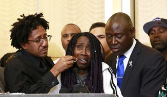 As Sequita Thompson, center, discusses the shooting of her grandson, Stephon Clark, Clark's brother, Ste' vonte Clark wipes a tear from her cheek during a news conference, Monday, March 26, 2018, in Sacramento, Calif. Clark, who was unarmed, was shot and killed by Sacramento police officers a week ago who were responding to a call about a person smashing car windows. At right is attorney Ben Crump. (AP Photo/Rich Pedroncelli)