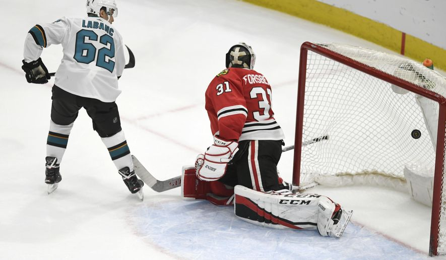 San Jose Sharks' Kevin Labanc (62) scores a goal against Chicago Blackhawks goalie Anton Forsberg (31), of Sweden, during a shootout in an NHL hockey game Monday, March 26, 2018, in Chicago. (AP Photo/Paul Beaty)