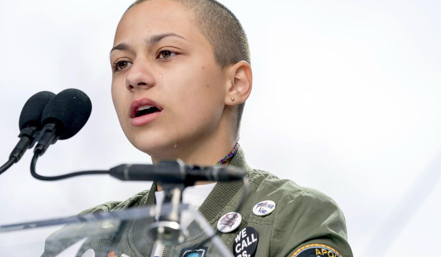 """FILE -- In this March 24, 2018 file photo, Emma Gonzalez, a survivor of the mass shooting at Marjory Stoneman Douglas High School in Parkland, Fla., closes her eyes and cries as she stands silently at the podium for the amount of time it took the Parkland shooter to go on his killing spree during the """"March for Our Lives"""" rally in support of gun control in Washington. A doctored photo online appeared to show Gonzalez tearing up the U.S. Constitution. , Saturday, March 24, 2018.  (AP Photo/Andrew Harnik File)"""