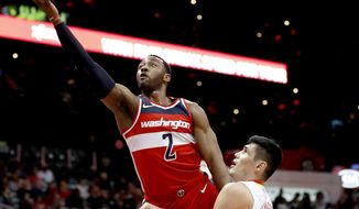 FILE - In this Dec. 27, 2017, file photo, Washington Wizards' John Wall, left, puts up a shot against Atlanta Hawks' Ersan Ilyasova, of Turkey, in the second quarter of an NBA basketball game in Atlanta. Wizards point guard John Wall says he feels good after a pair of full-contact practices but is not sure when he will return to game action for his struggling team. Wall spoke to reporters on Monday, March 26, 2018, his first remarks in Washington since having surgery on his left knee Jan. 31. (AP Photo/David Goldman, File)