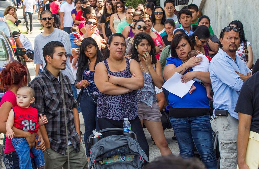 In this Aug. 15, 2012, file photo, a line of people living in the U.S. without legal permission wait outside the Coalition for Humane Immigrant Rights in Los Angeles. California is suing the Trump administration over its decision to add a question about citizenship to the 2020 U.S. Census. In announcing the lawsuit Tuesday, March 27, 2018, California Attorney General Xavier Becerra says adding such a question is a reckless decision that would violate the U.S. Constitution and cause a population undercount. (AP Photo/Damian Dovarganes, File)