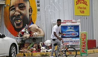 In this June 27, 2017 photo, Ronald Smith gets on his bicycle after stopping at the Triple S Food Mart, where Alton Sterling was shot by police one year ago, in Baton Rouge, La. A year later, visitors routinely stop by the Triple S Food Mart to photograph the iconic mural of Sterling's smiling face on its aluminum siding. A makeshift memorial — now reduced to soggy stuffed animals and withered flowers — still stands on the table where Sterling once sold homemade CDs outside. (AP Photo/Gerald Herbert)