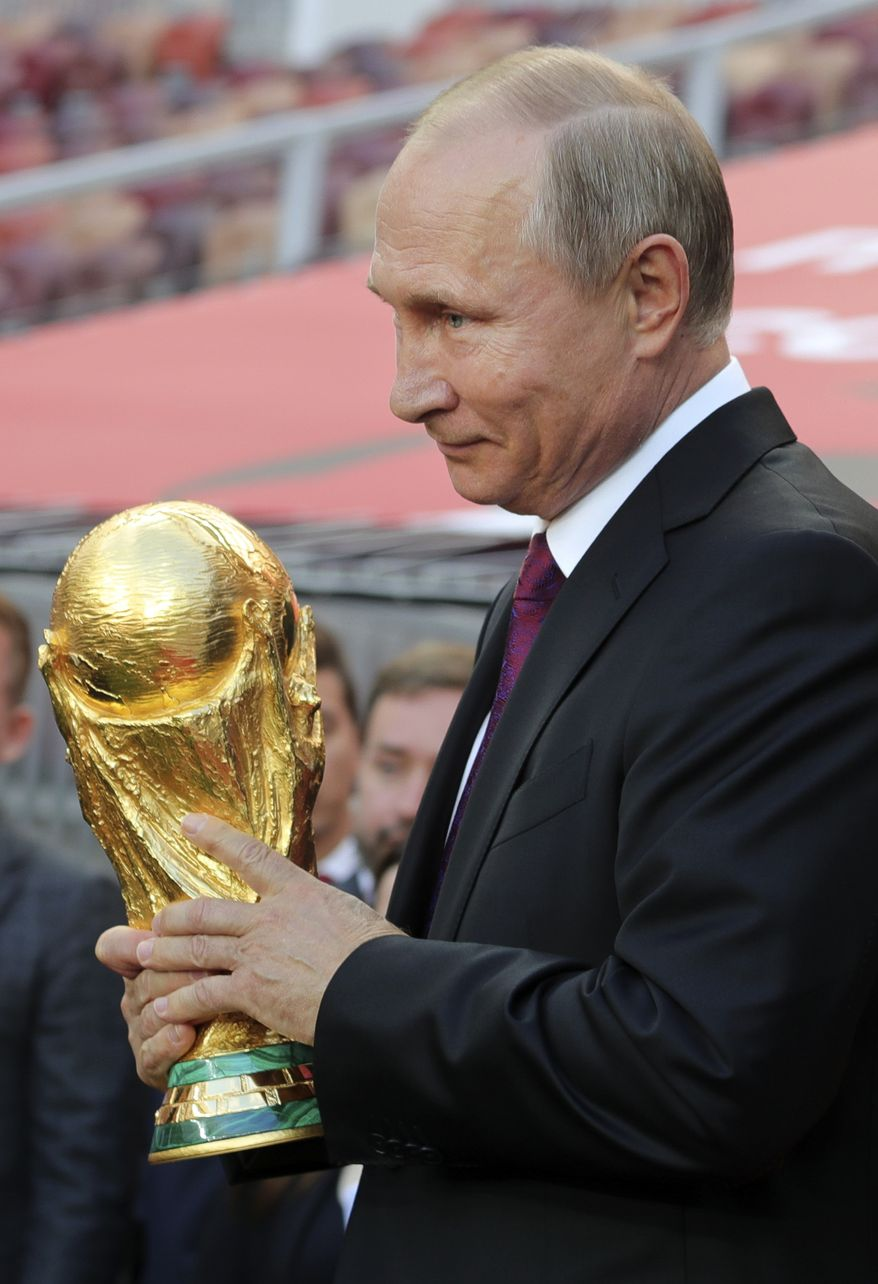 Russian President Vladimir Putin holds the FIFA World Cup trophy during its presentation at Moscow's Luzhniki Stadium, Russia, on Saturday, Sept. 9, 2017. From September 2017, the original trophy starts its tour over 24 Russian cities and more than 50 countries around the globe ahead of 2018 World Cup to start at Luzhniki stadium on June 14, 2018. (Mikhail Klimentyev, Sputnik, Kremlin Pool Photo via AP)