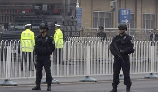 Heavily armed police guard an area outside a train station ahead of the arrival of a convoy in Beijing, China, Tuesday, March 27, 2018. The activity followed the arrival Monday of a train resembling one used by North Korea's previous leader, and a foreign guesthouse in Beijing had a heavy security presence overnight. Some media have speculated that North Korean leader Kim Jong-un was making a surprise visit to China. (AP Photo/Ng Han Guan)