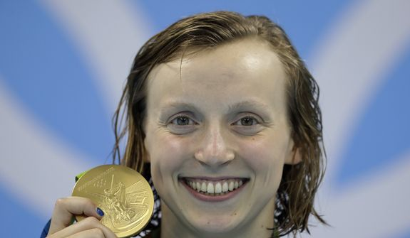 FILE - In this Aug. 9, 2016, file photo, United States' Katie Ledecky shows off her gold medal during the ceremony for the women's 200-meter freestyle final during the swimming competitions at the 2016 Summer Olympics, in Rio de Janeiro, Brazil. Ledecky is turning pro. The five-time Olympic gold medalist announced on Twitter that she is giving up her final two years of eligibility at Stanford, though she will continue to train at the West Coast school as she works toward her degree. (AP Photo/Michael Sohn, File) **FILE**