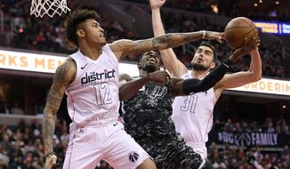 San Antonio Spurs guard Brandon Paul, center, goes to the basket against Washington Wizards forward Kelly Oubre Jr. (12) and guard Tomas Satoransky (31) during the second half of an NBA basketball game, Tuesday, March 27, 2018, in Washington. The Wizards won 116-106. (AP Photo/Nick Wass)