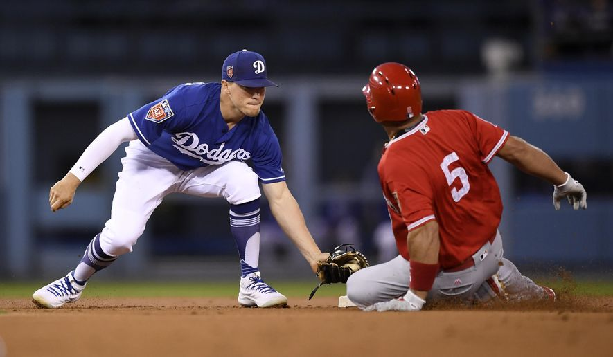 Los Angeles Dodgers second baseman Enrique Hernandez, left, tags out Albert Pujols at second as Pujols tried to stretch a single into a double during the first inning of a preseason baseball game Monday, March 26, 2018, in Los Angeles. (AP Photo/Mark J. Terrill)