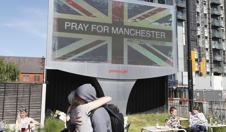 FILE - In this Tuesday May 23, 2017 file photo, couple embrace under a billboard in Manchester, England, the day after the suicide attack at an Ariana Grande concert that left more than 20 people dead. Firefighters were not allowed to go to the scene of the Manchester Arena bombing for more than two hours because of confusion about whether an attacker was still on the loose, according to an inquiry into the attack released Tuesday March 27, 2018. (AP Photo/Kirsty Wigglesworth, File)