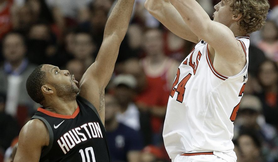 Chicago Bulls forward Lauri Markkanen, right, shoots as Houston Rockets guard Eric Gordon defends during the first half of an NBA basketball game Tuesday, March 27, 2018, in Houston. (AP Photo/Eric Christian Smith)