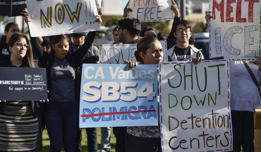 A small group of sanctuary state supporters gather outside the Orange County Board of Supervisors meeting in Santa Ana, Calif., as they prepare to discuss joining a DOJ lawsuit against the state of California on Tuesday, March 27, 2018. (Jeff Gritchen/The Orange County Register via AP)