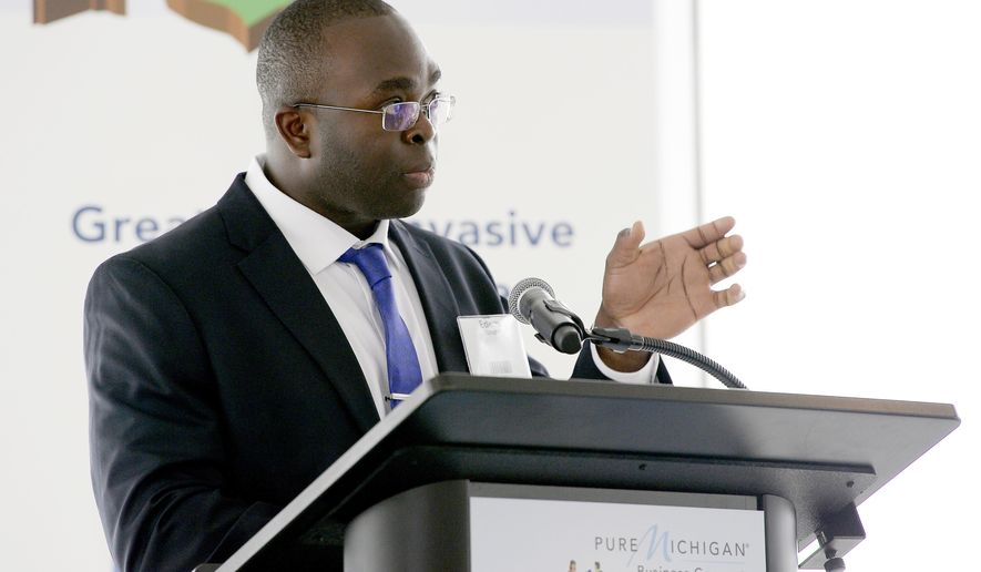 Edem Tsikata, a software consultant from Boston, gives his presentation  'A Cavitation Barrier to Deter Asian Carp,' during the Carp Tank event Tuesday, March 27, 2018, in Detroit. His presentation won the competition (Clarence Tabb Jr./Detroit News via AP)