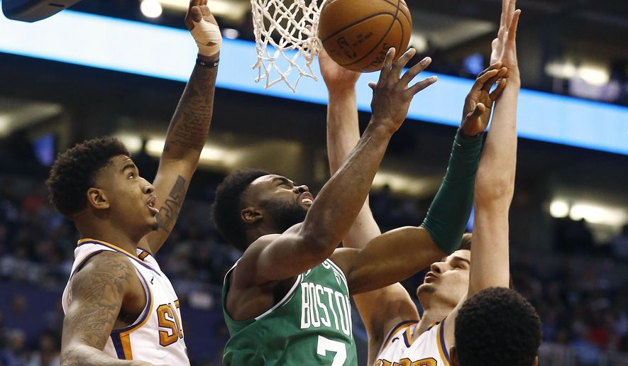 Boston Celtics guard Jaylen Brown (7) loses the ball as he tries to go up for a shot between Phoenix Suns forward Dragan Bender, right, and forward Marquese Chriss, left, during the first half of an NBA basketball game Monday, March 26, 2018, in Phoenix. (AP Photo/Ross D. Franklin)
