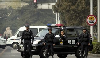 Police in tactical gear block a road leading to the Diaoyutai State Guesthouse in Beijing, Tuesday, March 27, 2018. Unusually heavy security at a Beijing guesthouse where prominent North Koreans have stayed in the past and media reports of a special train arriving have raised speculation that Kim Jong Un is making his first trip to China as North Korea's leader. (AP Photo/Mark Schiefelbein)