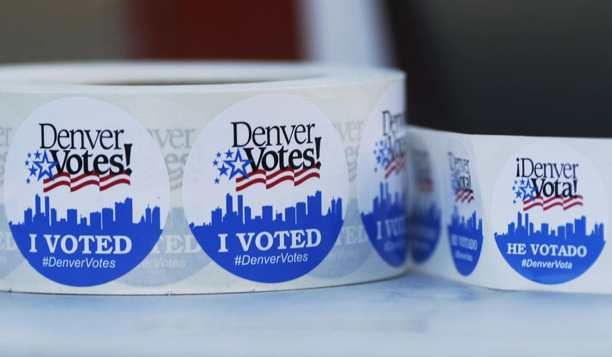 FILE - In this Nov. 8, 2016, file photo, rolls of stickers in English and Spanish sit on a table for distribution to motorists as they drop off ballots outside the Denver Election Commission headquarters in downtown Denver. A federal judge on Thursday, March 27, 2018, struck down a key element of Colorado's constitution that made it tougher for citizens to get proposed amendments onto the ballot. (AP Photo/David Zalubowski, File)