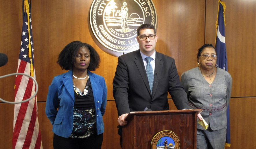 Florence, S.C., Mayor Stephen Wukela, center, talks about the shooting a a black driver by a white constable during a news conference Tuesday, March 27, 2018. He is joined by City Council members Teresa Myers Ervin, left, and Pat Gibson-Hye Moore, right. A volunteer police officer in South Carolina fired as many as eight bullets at a black driver last Saturday, who refused to get out of his vehicle during a traffic stop and appeared to be looking for something inside, a prosecutor said. (AP Photo/Jeffrey Collins)