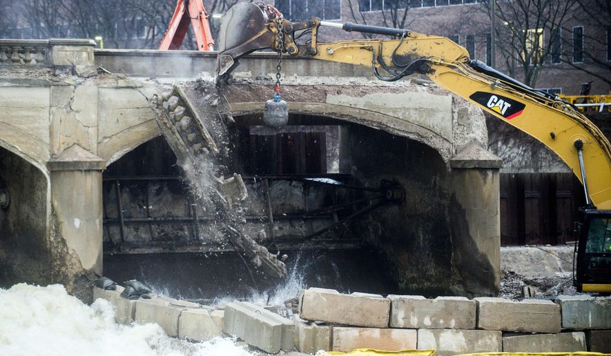 Pieces of concrete fall as a crew works to demolish the Hamilton Dam, Tuesday, March 27, 2018 in downtown Flint, Mich.. The demolition was initially scheduled for 2017, but it was moved back because the city needed to wait for Consumers Energy to finish dredging and capping the Flint River. The dredging of the Flint River was completed in late fall of 2017. (Jake May/The Flint Journal-MLive.com via AP)