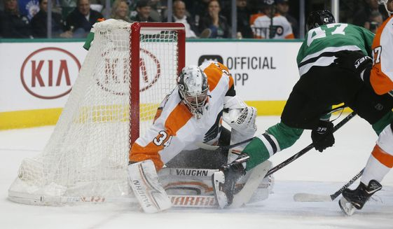Philadelphia Flyers goaltender Petr Mrazek (34) deflects a shot by Dallas Stars right wing Alexander Radulov (47) during the first period of an NHL hockey game in Dallas, Tuesday, March. 27, 2018. (AP Photo/Michael Ainsworth)