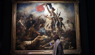"""A woman watches """"La liberte guidant le peuple"""" by Eugene Delacroix at the Louvre museum, in Paris, Tuesday, March 27, 2018. The Louvre is seeking to reinterpret the work of Eugene Delacroix in a retrospective that goes beyond the brief years in which he painted his most recognizable masterpieces such as """"Liberty Leading the People"""" that's graced postage stamps and bank notes in France as well as a Coldplay album cover. The exhibition runs from March 29 to July 23, 2018. (AP Photo/Christophe Ena)"""