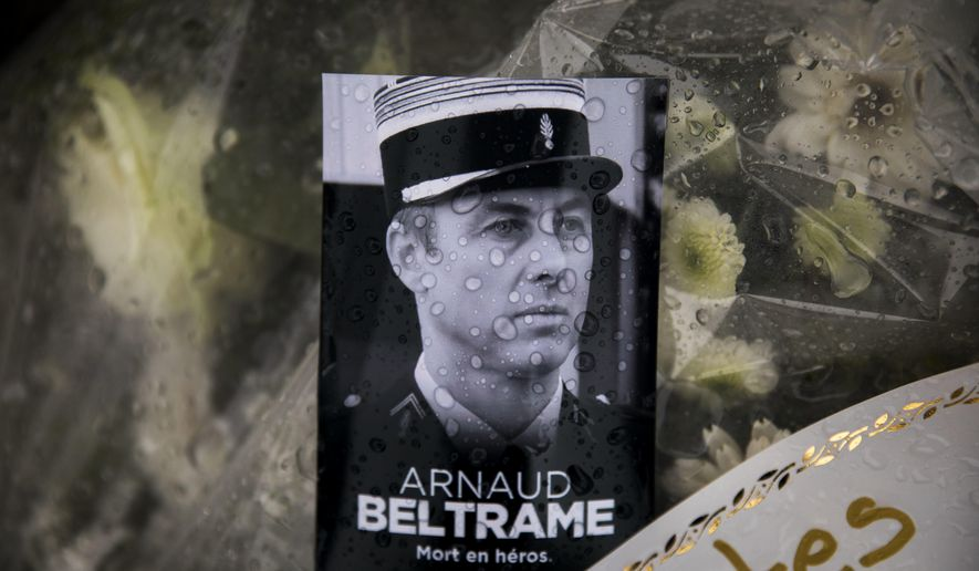 "A photo of Lieutenant Colonel Arnaud Beltrame placed on a bunch of flowers at the main gate of the Police headquarters in Carcassonne, France, Saturday, March 24, 2018, following an attack on a supermarket in Trebes in the south of the country on Friday. A French police officer who offered himself up to an Islamic extremist gunman in exchange for a hostage died of his injuries, raising the death toll in the attack to four, and the officer was honored Saturday as a national hero of ""exceptional courage and selflessness."" (AP Photo/Emilio Morenatti)"