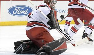 Carolina Hurricanes goaltender Scott Darling deflects the puck during the second period of an NHL hockey game against the New Jersey Devils Tuesday, March 27, 2018, in Newark, N.J. (AP Photo/Bill Kostroun)