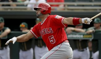FILE - In this Thursday, March 8, 2018, file photo, Los Angeles Angels' Albert Pujols watches his RBI-single against the Oakland Athletics during the first inning of a spring baseball game in Mesa, Ariz. With Pujols only 32 hits away from 3,000 in his career, this likely will be the fourth straight season a player joins the prestigious club. (AP Photo/Chris Carlson, File)