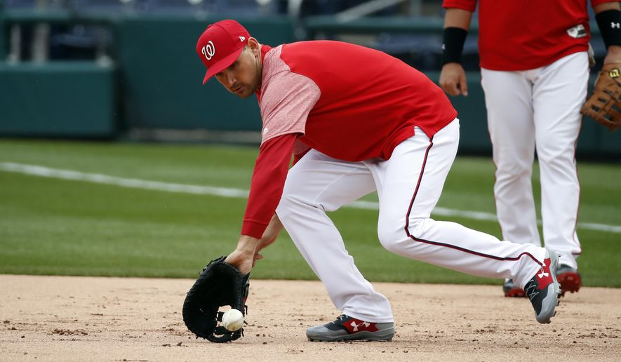 Washington Nationals first baseman Ryan Zimmerman snags a ground ball during warm ups before a spring exhibition baseball game against the Minnesota Twins at Nationals Park, Tuesday, March 27, 2018, in Washington. Zimmerman took a different approach to spring training, hitting on back fields and facing pitchers destined for the minor leagues instead of playing in Grapefruit League games. (AP Photo/Alex Brandon)
