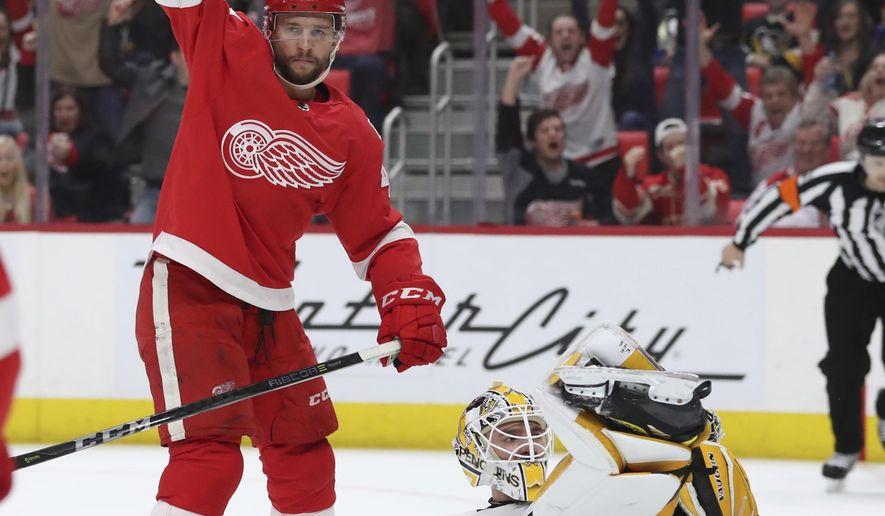 Detroit Red Wings right wing Luke Glendening raises his arm after scoring on Pittsburgh Penguins goaltender Matt Murray during the second period of an NHL hockey game Tuesday, March 27, 2018, in Detroit. (AP Photo/Carlos Osorio)