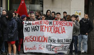 """FILE - In this Feb. 1, 2018 file photo, friends and supporters of rap singer Pablo Hasel, whose real surname is Rivadulla give him support at the National court where he appeared accused of tweeting messages between 2014-16 in defense of members of ETA and GRAPO, two armed groups ranked by Spain as terror organizations, and also insulting police in Madrid, Spain. Messages on banner read 'Without freedom of speech there is no democracy' 'Absolution for Pablo Hasel and Kaiet' Total amnesty'. The Madrid Booksellers' Guild is using a digital tool that automatically pulls around 80,000 words from Miguel de Cervantes' """"Don Quixote,"""" a classic of Spanish and western literature, to recreate online a recent court-banned book. The tool seeks to sidestep a judge's prohibition last month of the book that investigates drug-trafficking in Spain. (AP Photo/Paul White, File)"""