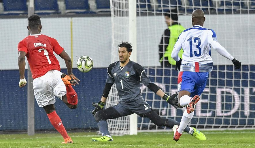 Switzerland's Breel Embolo, left, scores their third goal against Panama's goalkeeper Jaime Penedo, center, and Panama's Adolfo Machado during an international friendly soccer match between Switzerland and Panama at the Swisspor Arena, in Luzern, Switzerland, Tuesday, March 27, 2018. (Peter Schneider/Keystone via AP)