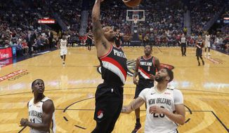 Portland Trail Blazers guard Damian Lillard slam dunks over New Orleans Pelicans guard Jrue Holiday, left, and forward Anthony Davis, in the first half of an NBA basketball game in New Orleans, Tuesday, March 27, 2018. (AP Photo/Gerald Herbert)