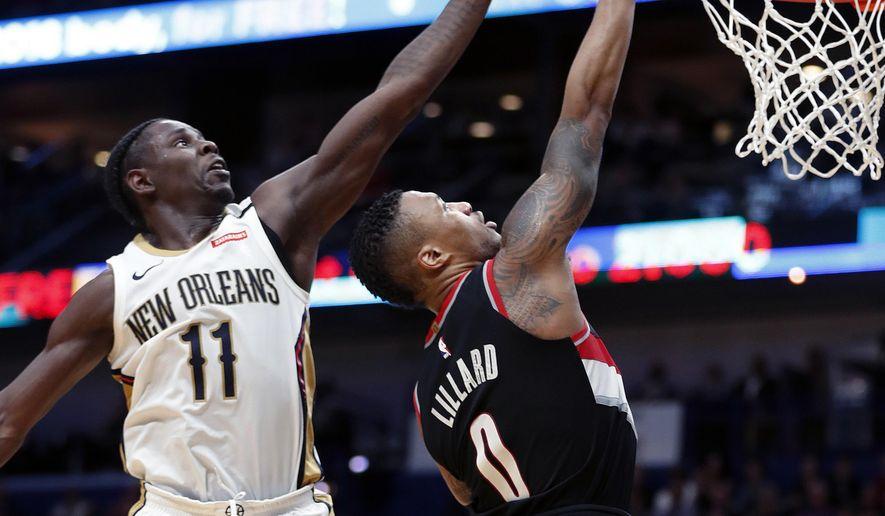 New Orleans Pelicans guard Jrue Holiday (11) blocks a shot by Portland Trail Blazers guard Damian Lillard (0) in the second half of an NBA basketball game in New Orleans, Tuesday, March 27, 2018. The Trail Blazers won 107-103. (AP Photo/Gerald Herbert)