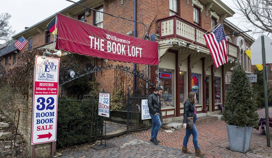 In this Feb. 17, 2018 photo, customers depart the entrance path at The Book Loft of German Village in Columbus, Ohio. The 40-year-old bookstore features 32 rooms of books. (AP Photo/Jonathan Elderfield)