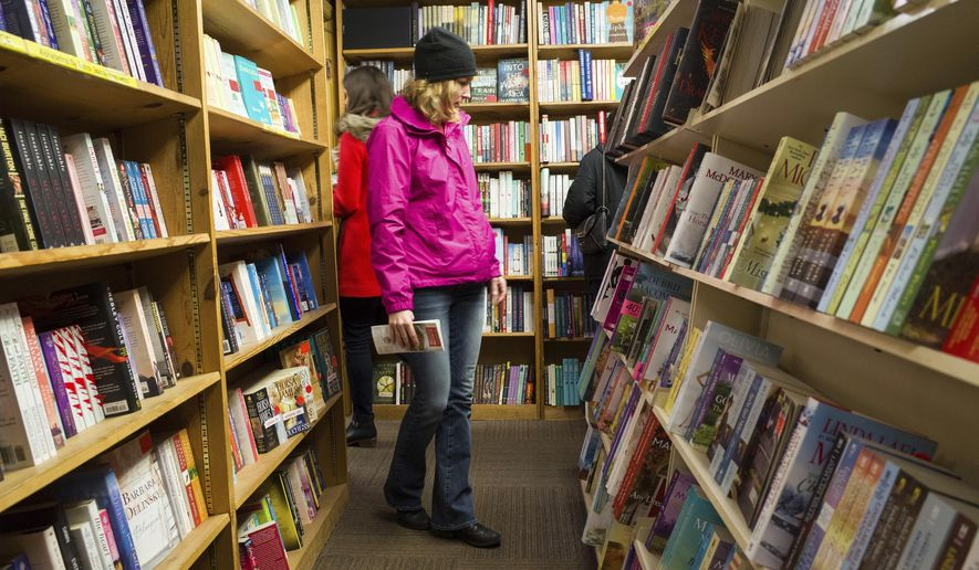 In this Feb. 17, 2018 file photo, shoppers browse among the narrow rows of books at The Book Loft of German Village in Columbus, Ohio.  **FILE**