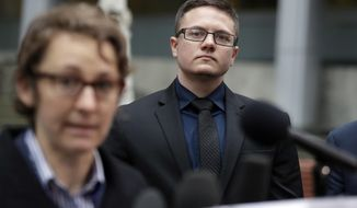 Plaintiff Conner Callahan, right, listens as attorney Natalie Nardecchia speaks to media members in front of a federal courthouse following a hearing there Tuesday, March 27, 2018, in Seattle. U.S. District Judge Marsha Pechman says she won't immediately consider President Donald Trump's new policy banning transgender people from serving in the military. Pechman is one of four federal judges who have issued orders blocking Trump's decision last year to overturn an Obama-era directive allowing transgender troops to serve openly. (AP Photo/Elaine Thompson)