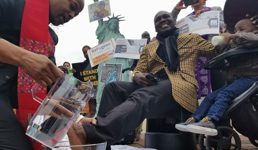 The Rev. Reuben Eckles washes Congolese refugee Beni Dedieu Luzau's feet on Wednesday. The Interfaith Immigration Coalition organized the ceremonial foot washing with refugees in front of the White House. (Julia Airey/The Washington Times)