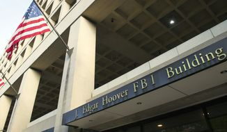 The FBI's J. Edgar Hoover Headquarters, across the street from the Justice Department in Washington, Wednesday, Nov. 2, 2016. (AP Photo/Cliff Owen) ** FILE **