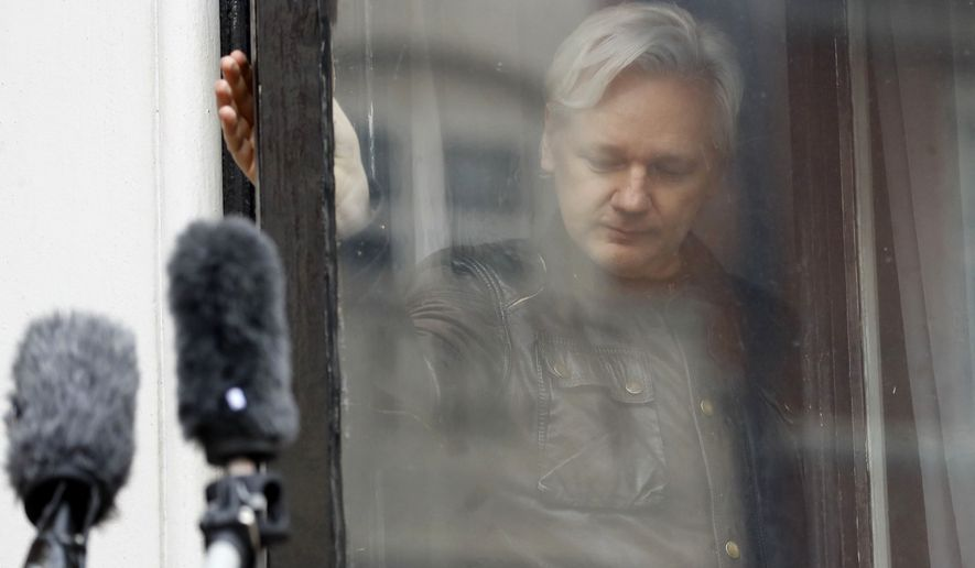 In this May 19, 2017, file photo, WikiLeaks founder Julian Assange closes a window after greeting supporters from the balcony of the Ecuadorian embassy in London. (AP Photo/Frank Augstein, File)