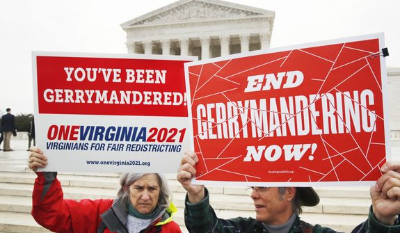 **FILE** Sara Fitzgerald, left, and Michael Martin, both with the group One Virginia, protest gerrymandering in front of the Supreme Court, Wednesday, March 28, 2018, in Washington where the court will hear arguments on a gerrymandering case. The Supreme Court is taking up its second big partisan redistricting case of the term amid signs the justices could place limits on drawing maps for political gain. (AP Photo/Jacquelyn Martin)