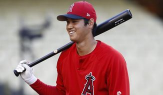 Los Angeles Angels starting pitcher Shohei Ohtani, of Japan, smiles during warmups before the team's preseason baseball game against the Los Angeles Dodgers, Tuesday, March 27, 2018, in Los Angeles. (AP Photo/Jae C. Hong)