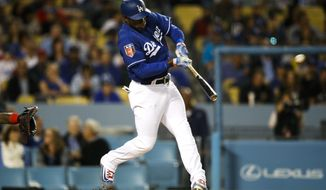 Los Angeles Dodgers' Yasiel Puig hits a home run during the first inning of an exhibition baseball game against the Los Angeles Angels, Tuesday, March 27, 2018, in Los Angeles. (AP Photo/Jae C. Hong)