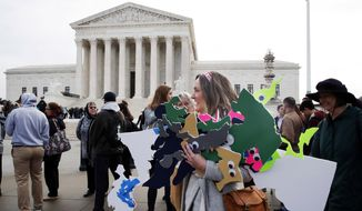 In this file photo, Ashley Oleson, with the League of Women Voters of Maryland, carries signs of Maryland's districts, as nonpartisan groups against gerrymandering protest in front of the Supreme Court, Wednesday, March 28, 2018, in Washington where the court will hear arguments on a gerrymandering case.  (AP Photo/Jacquelyn Martin) **FILE**
