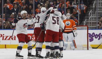 Columbus Blue Jackets players celebrate a goal as Edmonton Oilers goalie Cam Talbot (33) looks on during second period NHL hockey action in Edmonton, Alberta, on Tuesday March 27, 2018. (Jason Franson/The Canadian Press via AP)