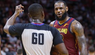 Cleveland Cavaliers forward LeBron James (23) argues a call with referee James Williams in the fourth quarter of play against the Miami Heat during an NBA basketball game, Tuesday, March 27, 2018, in Miami. The Heat won the game 98-79. (AP Photo/Joe Skipper)