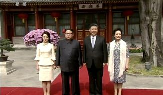 In this image taken from video footage run Wednesday, March 28, 2018, by China's CCTV via AP Video, North Korean leader Kim Jong Un, center left, and his wife Ri Sol Ju, left, Chinese counterpart Xi Jinping, center right, and his wife Peng Liyuan pose for a photo at Diaoyutai State Guesthouse in Beijing. North Korea's leader Kim and his Chinese counterpart Xi sought to portray strong ties between the neighbors and long-time allies despite a recent chill, as both countries on Wednesday confirmed Kim's secret trip to Beijing this week. (CCTV via AP Video)