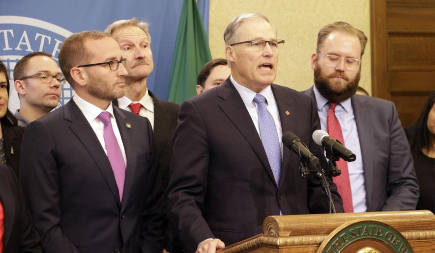 Gov. Jay Inslee, center, speaks before signing a bill banning licensed therapists from trying to change a minor's sexual orientation, on Wednesday, March 28, 2018, in Olympia, Wash. Washington joins 10 other states, including California and Oregon, plus the District of Columbia that have laws or regulations banning conversion therapy for LGBT minors. (AP Photo/Rachel La Corte)