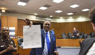 Richard Phillips shows his order of dismissal of homicide charges against him in Judge kevin Cox's courtroom at the Frank Murphy Hall of Justice in Detroit on Wednesday, March 28, 2018. Phillips, whose murder conviction was thrown out after he spent 45 years in prison, was exonerated Wednesday and won't face a second trial. (Max Ortiz/Detroit News via AP)